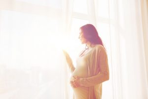 close up of happy pregnant woman with big belly looking to window